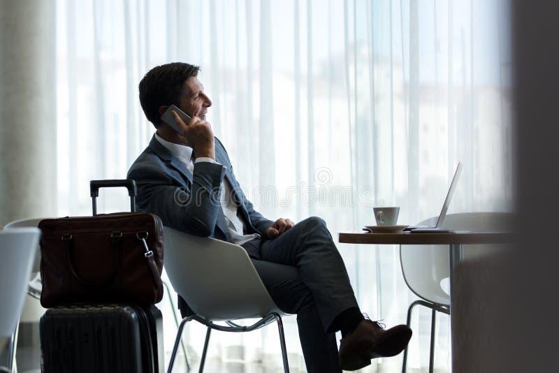 Επιχειρηματίας στο σαλόνι αερολιμένων που μιλά στο τηλέφωνο στοκ εικόνες με δικαίωμα ελεύθερης χρήσης