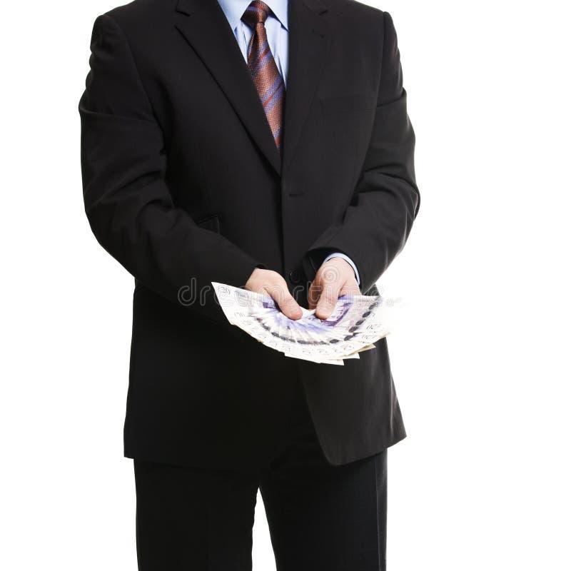 Επιχειρηματίας στο σκοτεινό κοστούμι με μια δέσμη των βρετανικών λιρών αγγλίας στοκ εικόνα με δικαίωμα ελεύθερης χρήσης