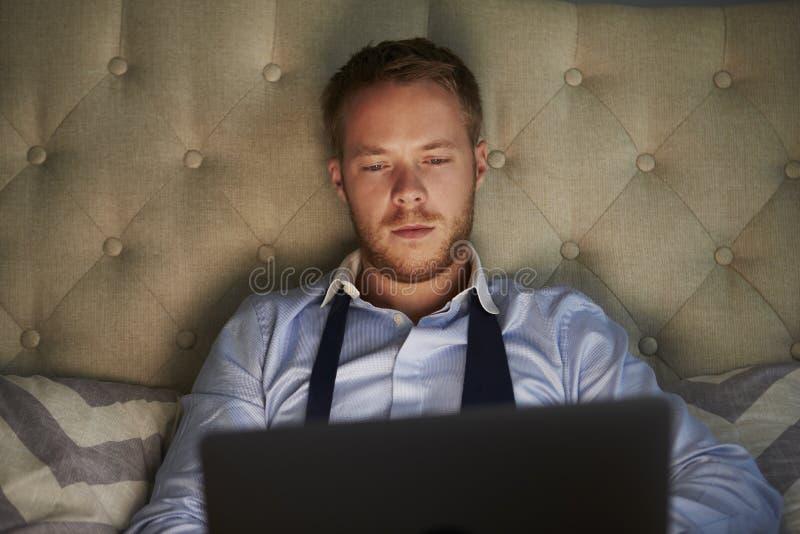 Επιχειρηματίας στο σπίτι στο κρεβάτι που λειτουργεί αργά στο lap-top στοκ εικόνες
