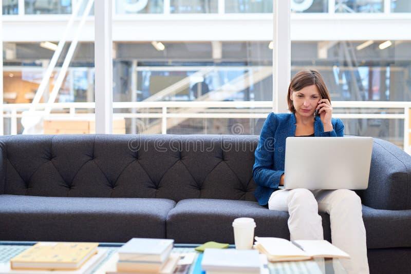 Επιχειρηματίας στο σύγχρονο γραφείο στον καναπέ με το τηλέφωνο και το lap-top στοκ φωτογραφίες