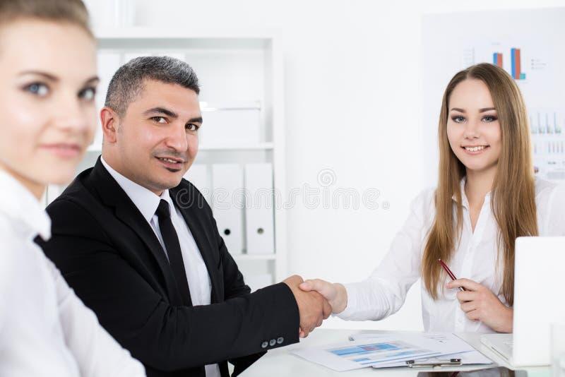 Επιχειρηματίας στο χέρι της επιχειρησιακής γυναίκας τινάγματος κοστουμιών στοκ εικόνα
