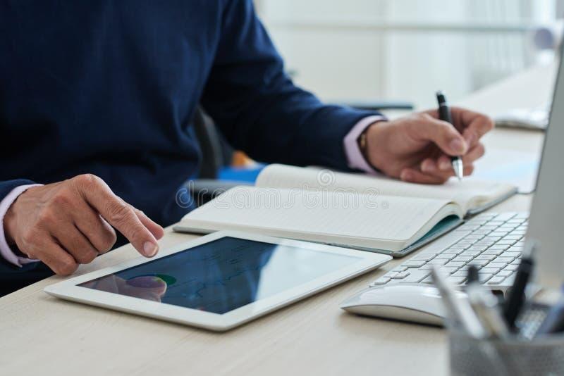 Επιχειρηματίας συγκομιδών χρησιμοποιώντας την ταμπλέτα και κάνοντας τις σημειώσεις στοκ εικόνα με δικαίωμα ελεύθερης χρήσης
