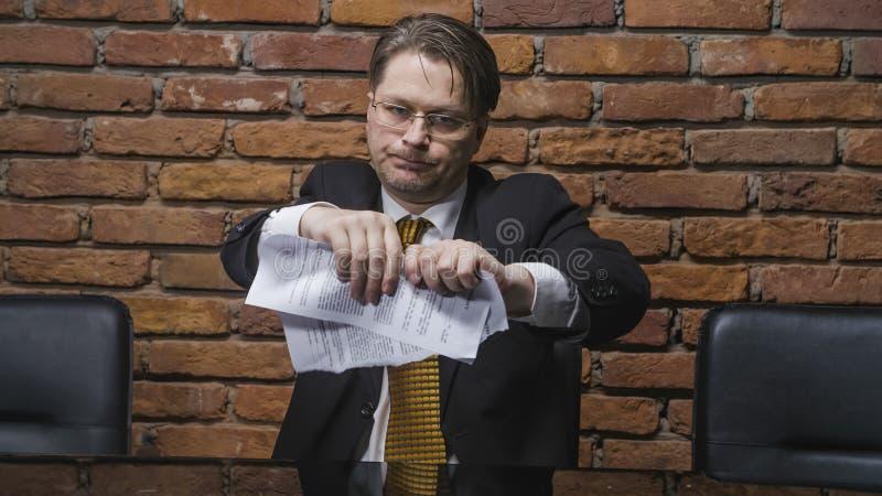 Επιχειρηματίας λυσσασμένος μια σύμβαση στα κομμάτια στοκ φωτογραφίες
