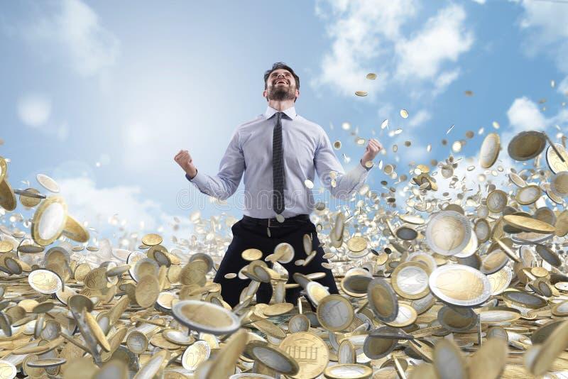 Επιχειρηματίας exults πέρα από πολλά νομίσματα χρημάτων στοκ φωτογραφίες