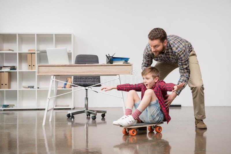 Επιχειρηματίας freelancer που έχει τη διασκέδαση με το γιο skateboard στοκ εικόνα