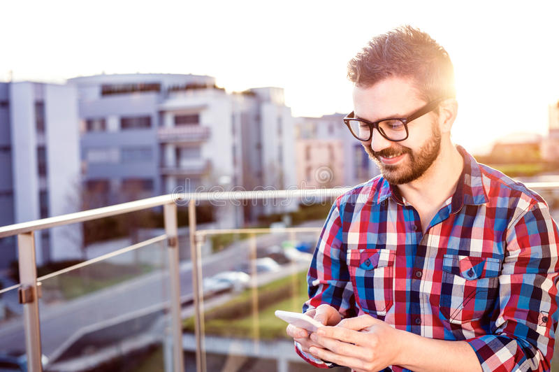 Επιχειρηματίας Hipster με έξυπνο τηλεφωνικό, που στέκεται στο balcon στοκ φωτογραφίες με δικαίωμα ελεύθερης χρήσης