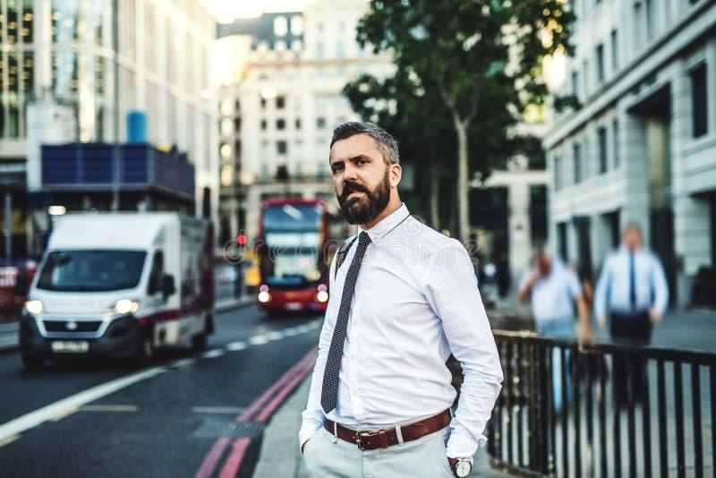 Επιχειρηματίας Hipster που στέκεται στην οδό στο Λονδίνο δίπλα σε έναν πολυάσχολο δρόμο στοκ φωτογραφίες