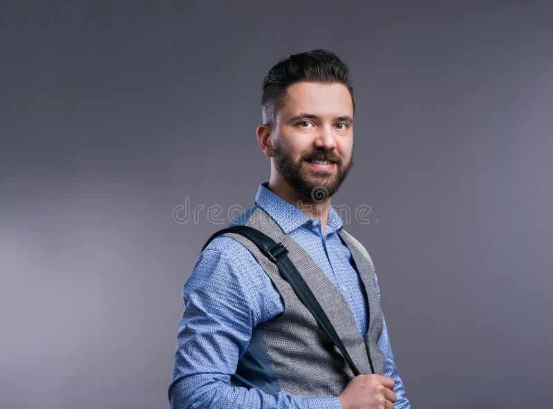 Επιχειρηματίας Hipster στο μπλε πουκάμισο, στούντιο πυροβοληθε'ν, γκρίζο υπόβαθρο στοκ εικόνα με δικαίωμα ελεύθερης χρήσης