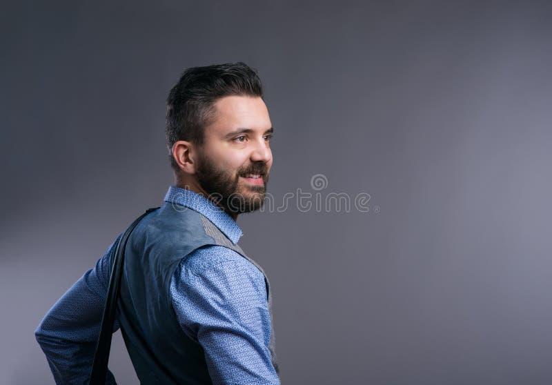 Επιχειρηματίας Hipster στο μπλε πουκάμισο, στούντιο πυροβοληθε'ν, γκρίζο υπόβαθρο στοκ φωτογραφίες με δικαίωμα ελεύθερης χρήσης