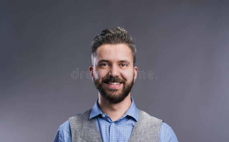 Επιχειρηματίας Hipster στο μπλε πουκάμισο, στούντιο πυροβοληθε'ν, γκρίζο υπόβαθρο στοκ εικόνα