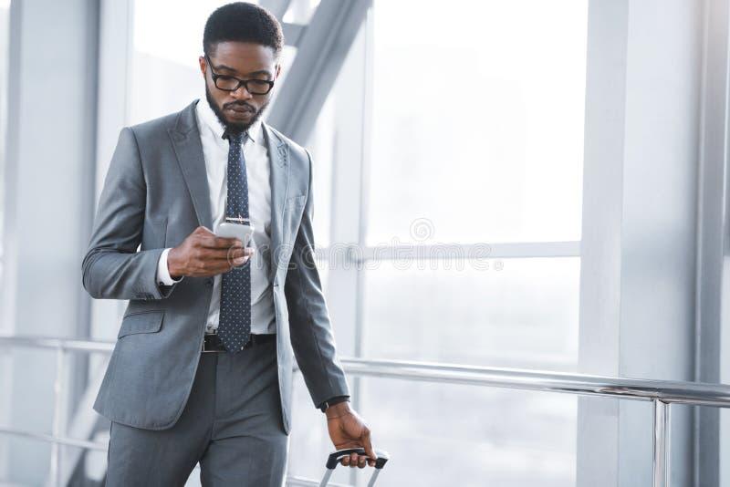 Επιχειρηματίας Texting σε Smartphone που περπατά στο τερματικό αερολιμένων στοκ εικόνες
