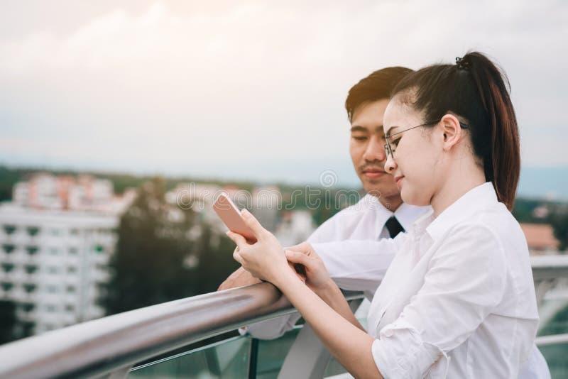 Επιχειρηματίες ζεύγους που χρησιμοποιούν το smartphone από κοινού στοκ φωτογραφία