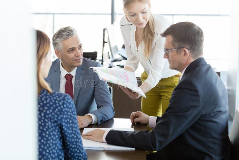 Επιχειρηματίες και επιχειρηματίες στη συζήτηση με το πρόγραμμα στο δωμάτιο πινάκων στοκ εικόνες