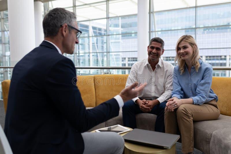 Επιχειρηματίες Καυκασίων που αλληλεπιδρούν ο ένας με τον άλλον στον καναπέ στοκ εικόνες