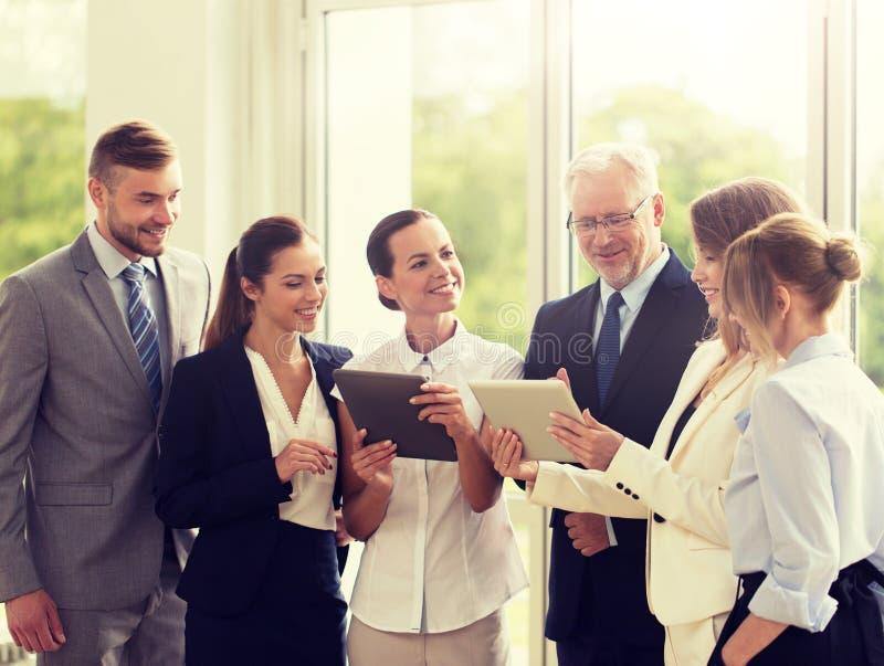 Επιχειρηματίες με τους υπολογιστές PC ταμπλετών στο γραφείο στοκ φωτογραφίες