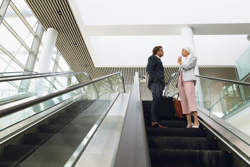 """Επιχειρηματίες με τσάντες να συνομιλούν μεταξύ Ï""""Î¿Ï…Ï' σε κυλιόμενη σκάλΠστοκ φωτογραφίες με δικαίωμα ελεύθερης χρήσης"""