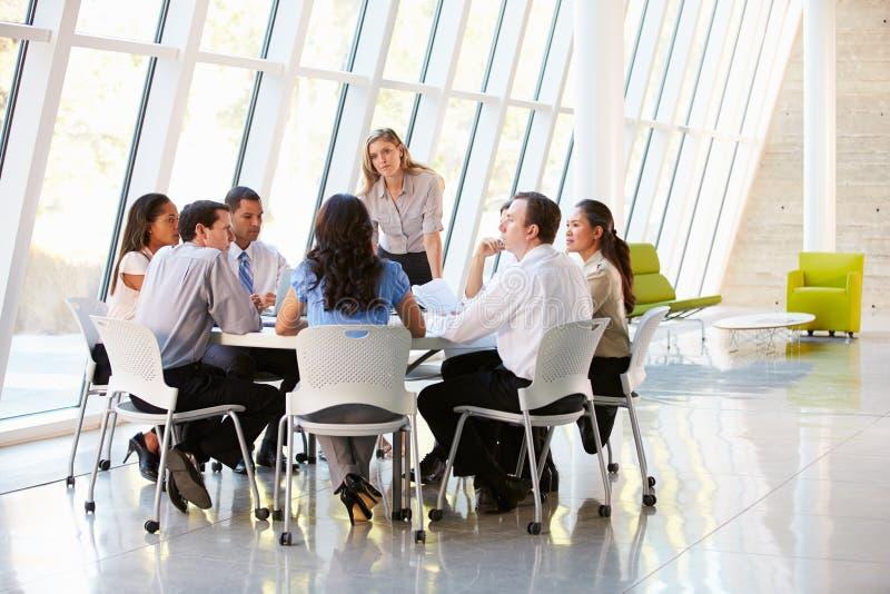 Επιχειρηματίες που έχουν τη συνεδρίαση Συμβουλίου στο σύγχρονο γραφείο στοκ φωτογραφίες
