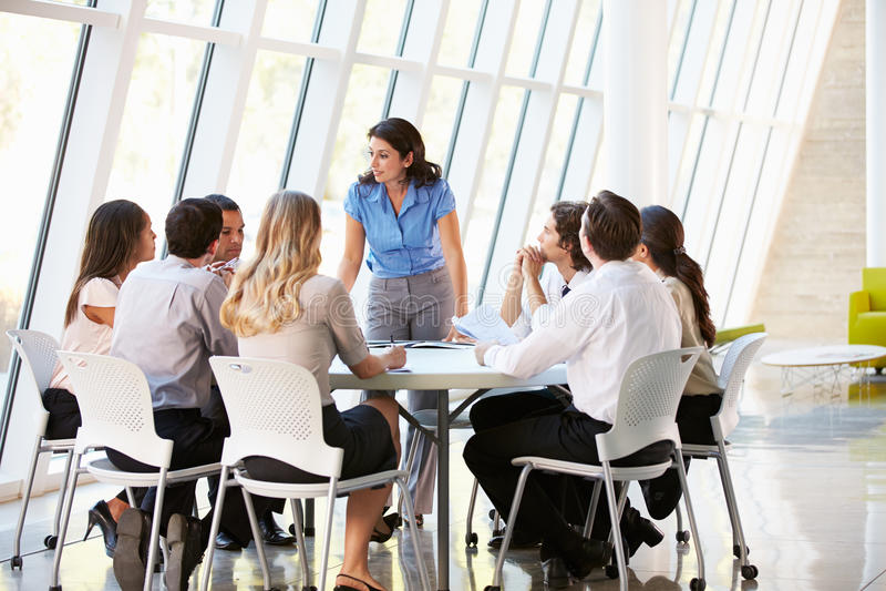 Επιχειρηματίες που έχουν τη συνεδρίαση Συμβουλίου στο σύγχρονο γραφείο στοκ φωτογραφία