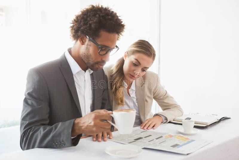 Επιχειρηματίες που έχουν τον καφέ που εξετάζει την εφημερίδα στοκ εικόνες με δικαίωμα ελεύθερης χρήσης