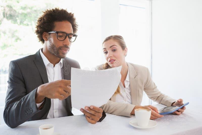 Επιχειρηματίες που έχουν τον καφέ που εξετάζει το αρχείο στοκ εικόνα