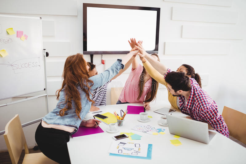 Επιχειρηματίες που δίνουν υψηλός-πέντε μαζί στη συνεδρίαση στο δημιουργικό γραφείο στοκ φωτογραφίες με δικαίωμα ελεύθερης χρήσης