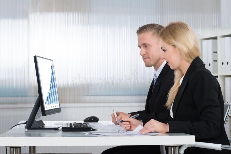 Επιχειρηματίες που αναλύουν τη γραφική παράσταση στη οθόνη υπολογιστή στην αρχή στοκ εικόνα