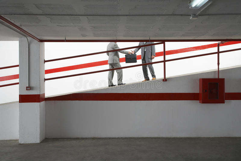 Επιχειρηματίες που ανταλλάσσουν το χαρτοφύλακα στην κεκλιμένη ράμπα στο γκαράζ χώρων στάθμευσης στοκ φωτογραφίες
