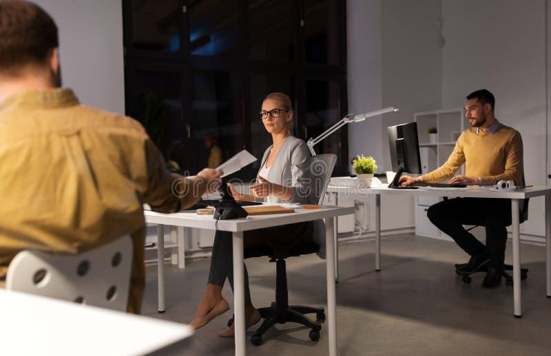 Επιχειρηματίες που απασχολούνται αργά τη νύχτα στο γραφείο στοκ φωτογραφίες