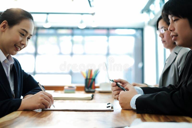 Επιχειρηματίες που απασχολούνται και που συζητούν στο νέο πρόγραμμα σχεδίων στην αρχή και που βάζουν την υπογραφή για το έγγραφο, στοκ φωτογραφία