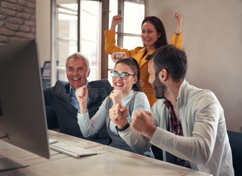 Επιχειρηματίες που γιορτάζουν τα επιτυχή προγράμματα στοκ εικόνες