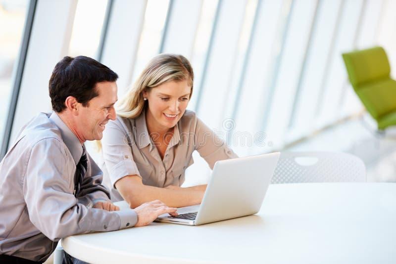 Επιχειρηματίες που διοργανώνουν τη συνεδρίαση γύρω από τον πίνακα στο σύγχρονο γραφείο στοκ εικόνα με δικαίωμα ελεύθερης χρήσης