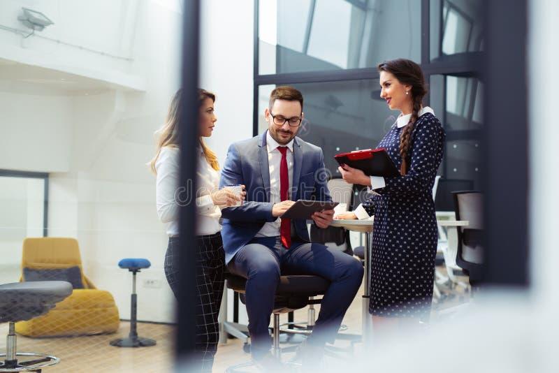 Επιχειρηματίες που διοργανώνουν τη συνεδρίαση στο σύγχρονο γραφείο στοκ εικόνες