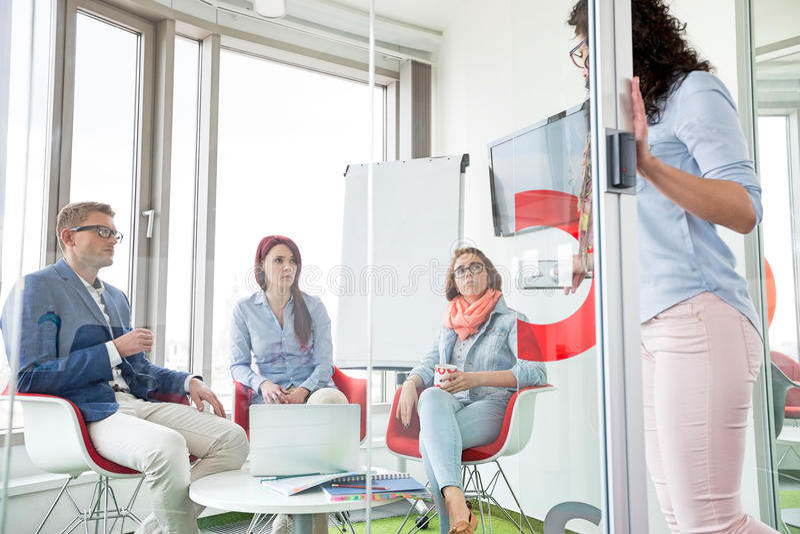 Επιχειρηματίες που εξετάζουν τη γυναίκα συνάδελφος που στέκεται στη συρόμενη πόρτα στοκ εικόνα με δικαίωμα ελεύθερης χρήσης