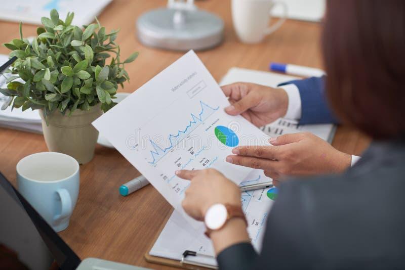 Επιχειρηματίες που εξετάζουν τις οικονομικές γραφικές παραστάσεις στοκ φωτογραφία με δικαίωμα ελεύθερης χρήσης