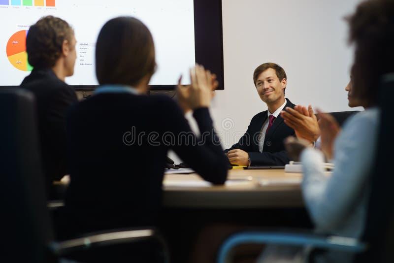 Επιχειρηματίες που επιδοκιμάζουν το διευθυντή που κάνει την παρουσίαση στη συνεδρίαση στοκ φωτογραφία με δικαίωμα ελεύθερης χρήσης
