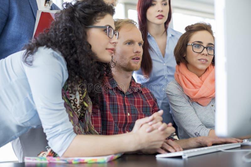 Επιχειρηματίες που εργάζονται μαζί στον υπολογιστή στην αρχή στοκ φωτογραφία με δικαίωμα ελεύθερης χρήσης