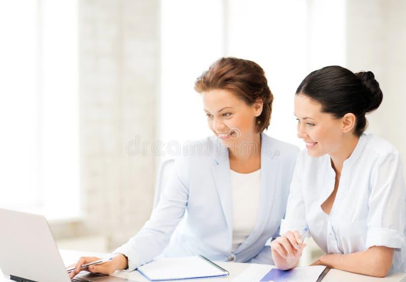 Επιχειρηματίες που εργάζονται με το lap-top στην αρχή στοκ εικόνα