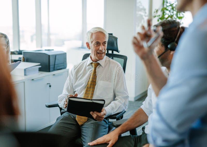 Επιχειρηματίες που διοργανώνουν μια συνεδρίαση στην αρχή στοκ φωτογραφία με δικαίωμα ελεύθερης χρήσης
