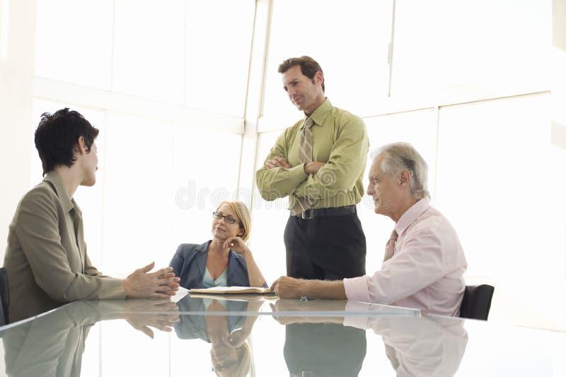 Επιχειρηματίες που διοργανώνουν τη συζήτηση στον πίνακα διασκέψεων στοκ εικόνες με δικαίωμα ελεύθερης χρήσης