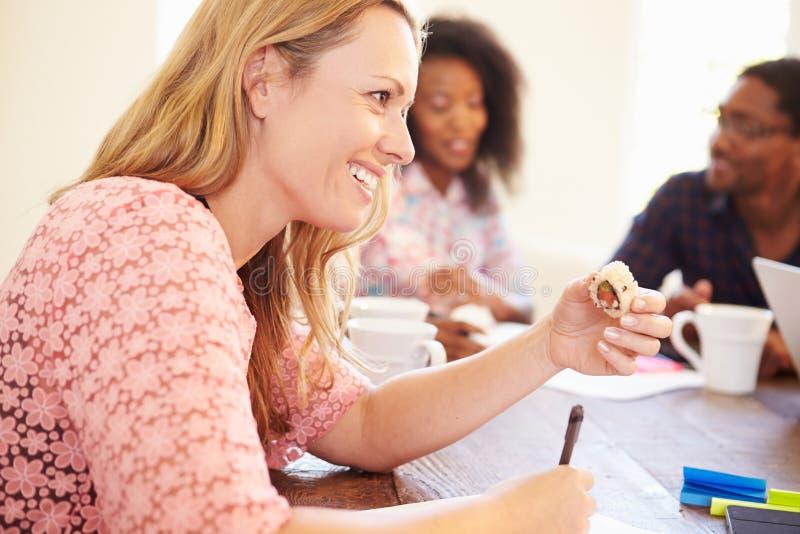 Επιχειρηματίες που διοργανώνουν τη συνεδρίαση και που τρώνε τα σούσια στοκ φωτογραφία