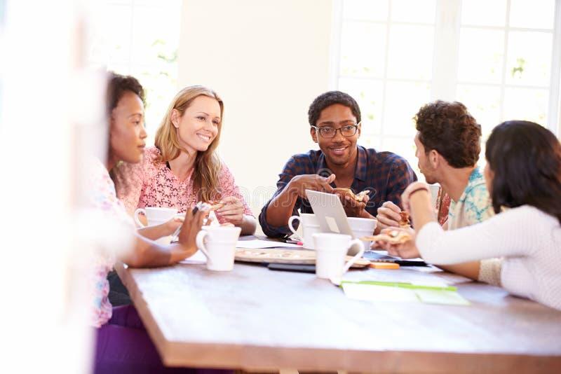 Επιχειρηματίες που διοργανώνουν τη συνεδρίαση και που τρώνε την πίτσα στοκ εικόνες