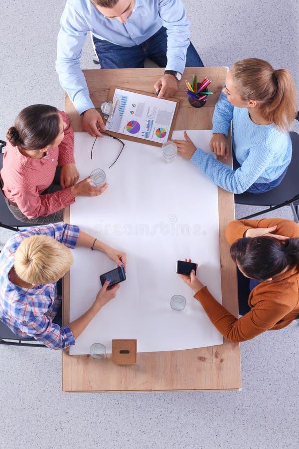 Επιχειρηματίες που κάθονται και που συζητούν στη συνεδρίαση, στην αρχή στοκ εικόνα