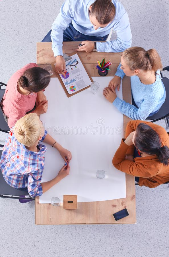 Επιχειρηματίες που κάθονται και που συζητούν στη συνεδρίαση, στην αρχή στοκ φωτογραφίες με δικαίωμα ελεύθερης χρήσης