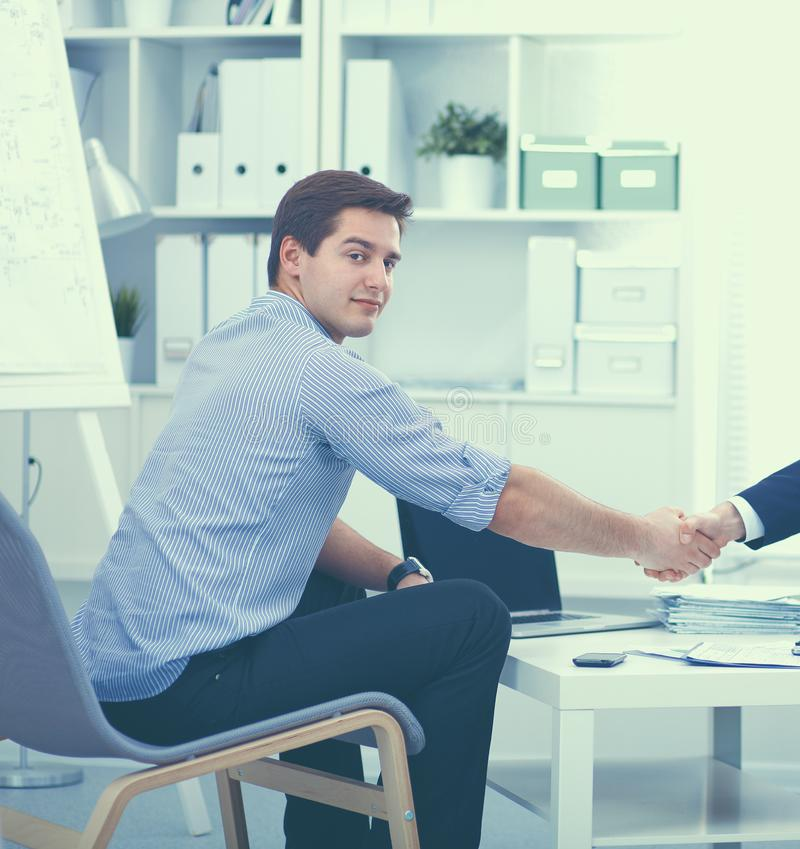 Επιχειρηματίες που κάθονται και που συζητούν στη συνεδρίαση, στην αρχή στοκ εικόνες