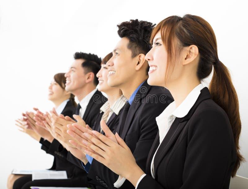 Επιχειρηματίες που κάθονται σε μια σειρά και μια επιδοκιμασία στοκ φωτογραφία