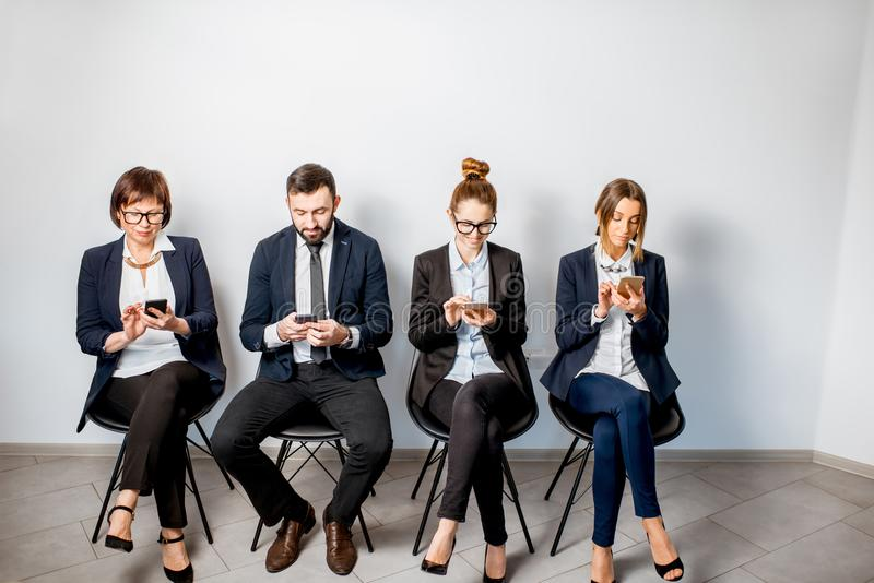 Επιχειρηματίες που κάθονται σε μια σειρά στοκ εικόνες με δικαίωμα ελεύθερης χρήσης