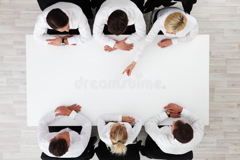 Επιχειρηματίες που κάθονται τον κενό πίνακα στοκ φωτογραφία