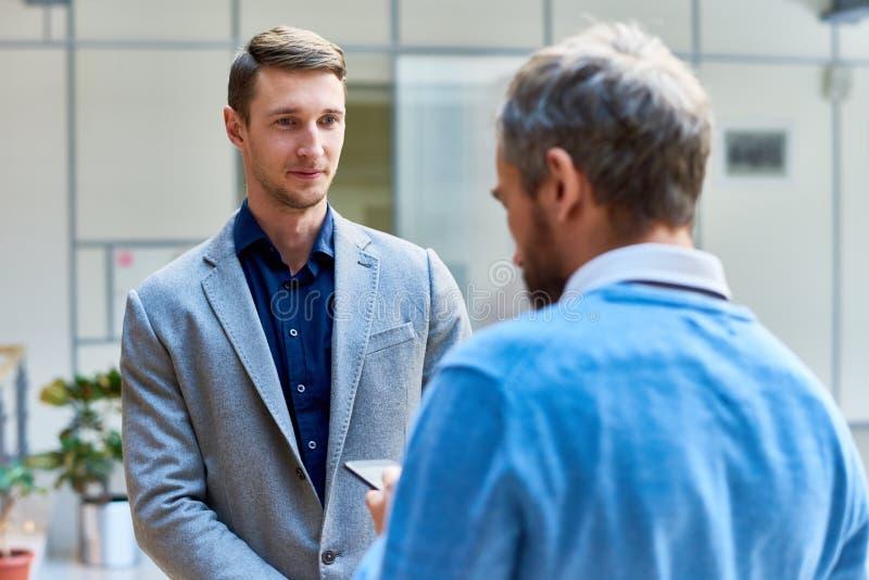 Επιχειρηματίες που κουβεντιάζουν στην αίθουσα στοκ φωτογραφία με δικαίωμα ελεύθερης χρήσης