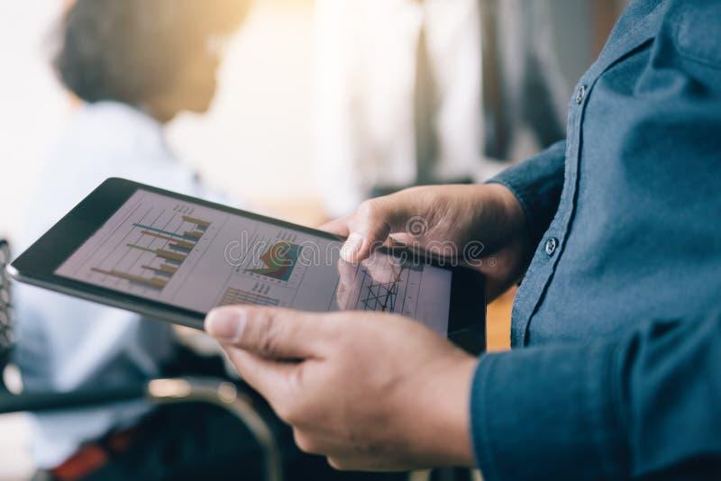 Επιχειρηματίες που κρατούν την ταμπλέτα και που φαίνονται διάγραμμα συνοπτικών εκθέσεων στοκ φωτογραφία με δικαίωμα ελεύθερης χρήσης