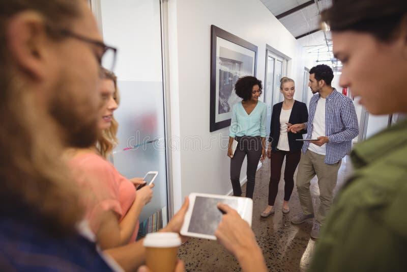 Επιχειρηματίες που μιλούν περπατώντας στο διάδρομο στοκ φωτογραφίες με δικαίωμα ελεύθερης χρήσης